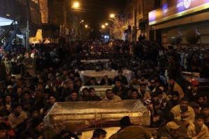 Haunting photo of grieving protestors sitting with coffins in the freezing cold in Quetta