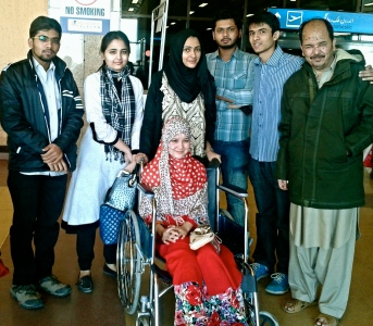 Kauser Ali Hazara (right) and his daughter Mehrin Kauser (in wheelchair) at Karachi airport with volunteers, headed back to Quetta where they would learn of the loss of their loved ones.