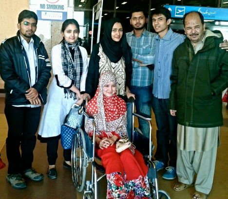 Kauser Ali Hazara (right) and his daughter Mehrin Kauser (in wheelchair) at Karachi airport with volunteers, headed back to Quetta where they learned of the loss of their loved ones.