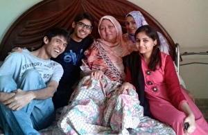 Nasrin Fatima (centre) lost her only daughter, Sadaf, 20. She had badly fractured feet, and still needs skin draft operations. Pictured here, April 2014, with the volunteers.