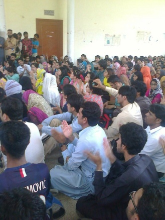 Karachi University students and faculty crowd the lobby outside the Arts Auditorium, locked by the administration